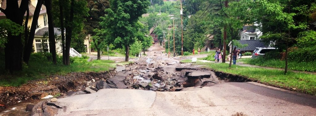 a steep road ripped up by water resulting in a street-wide sized hole
