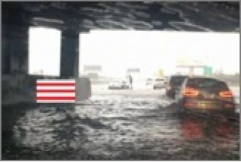flooded parking garage with red and white gauge overlay in center left
