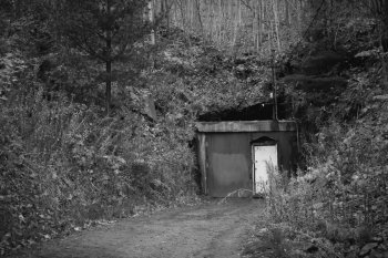 The door to Quincy Mine set into a hillside in a black and white photo with the doors closed.