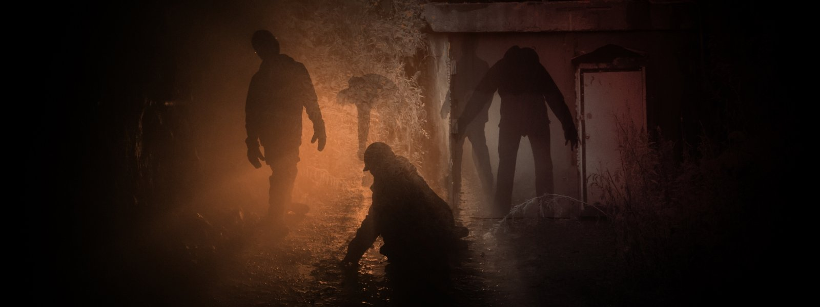 the shadow of zombielike figures wearing hard hats in a hazy red lit dark tunnel underground in a haunted mine.