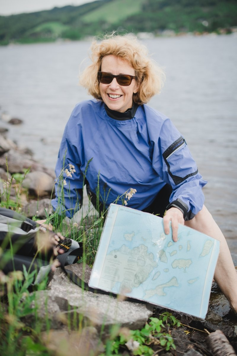 A woman sitting on rocks on the shore of a canal/river holding a map of lake superior and a waterproof bag, wearing sunglasses and smiing