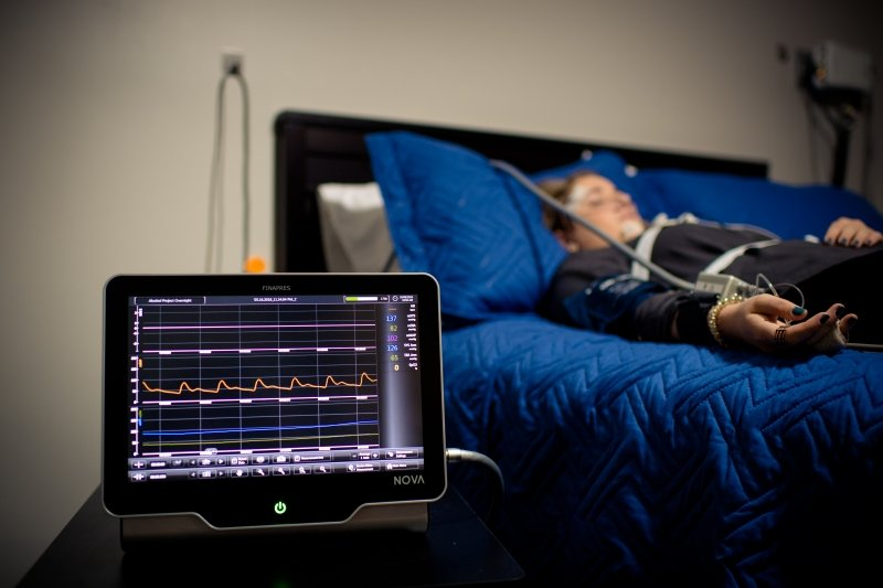 person sleeping on a bed behind a tablet with a medical display