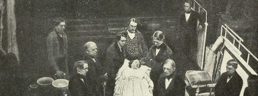 A historical photo of a group of men at Harvard clustered around a female patient on an operating table.