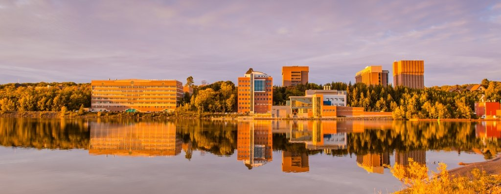 Michigan Tech campus in fall reflected off Portage Canal