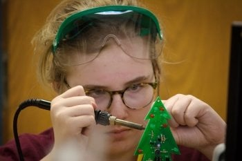 A young woman concentrates on making a circuit board that is green