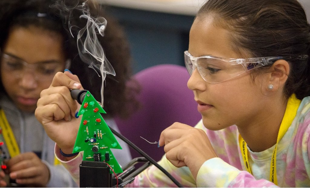 two young girls working on green pine-tree shaped circuit boards, wearing safety glasses, with the girl in the foreground using a soldering iron.