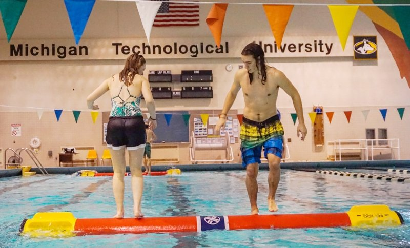 A female and a male student stand on a red log in an indoor swimming pool that's regulation size. Her back is to us, he is facing us, they are looking at each other's feet as they roll the log.