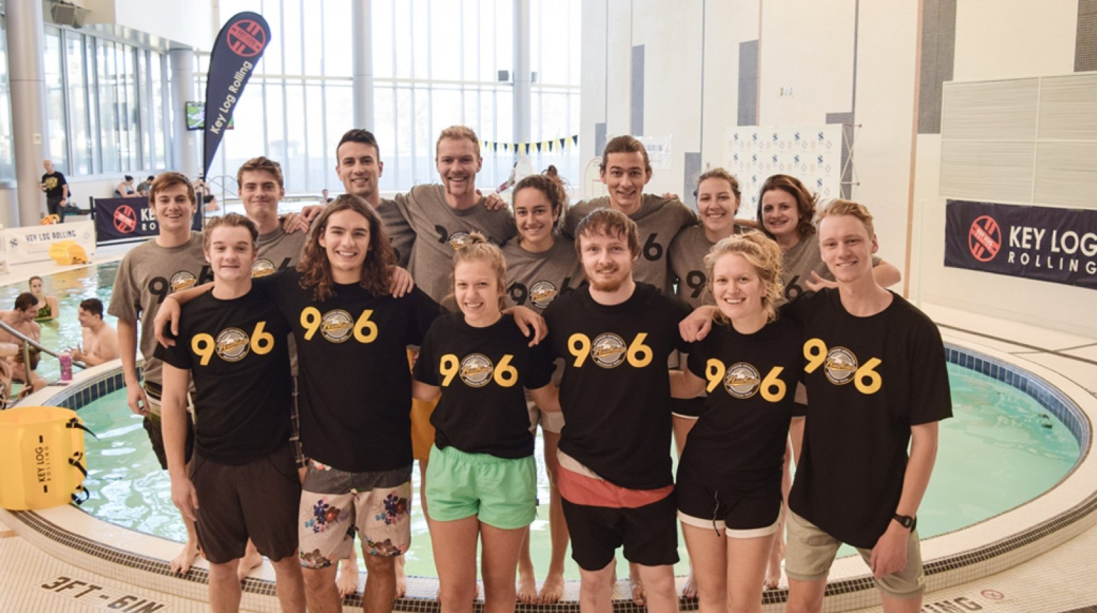 Students stand in a group wearing 906 T-shirts and shorts and bathing suits in front of an indoor pool at a log-rolling competition.