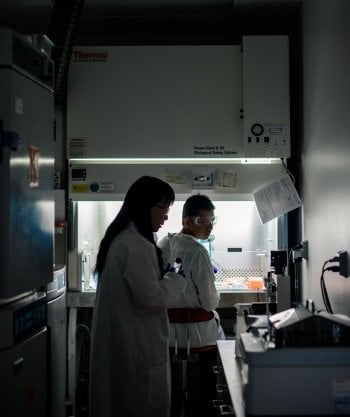 people in labs backlit next to a chemical exhaust hood