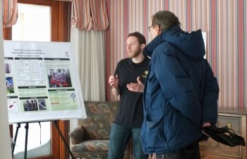 A young man talks to an older man showing him a poster of a composting project in a house with pink striped wallpaper with snow outside.