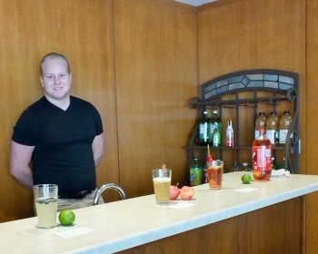 A young man stands behind a wooden bar with wood paneling in the background with soft drinks, glasses and fruit on the bar.