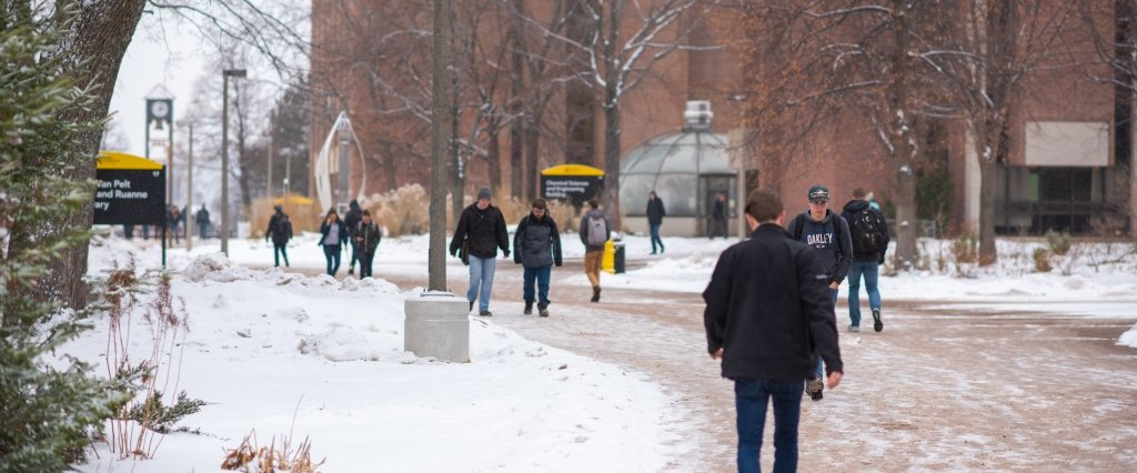 Students walking across campus while snow is falling.
