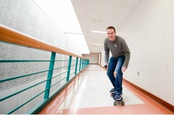 man on a skateboard in an academic building hallway
