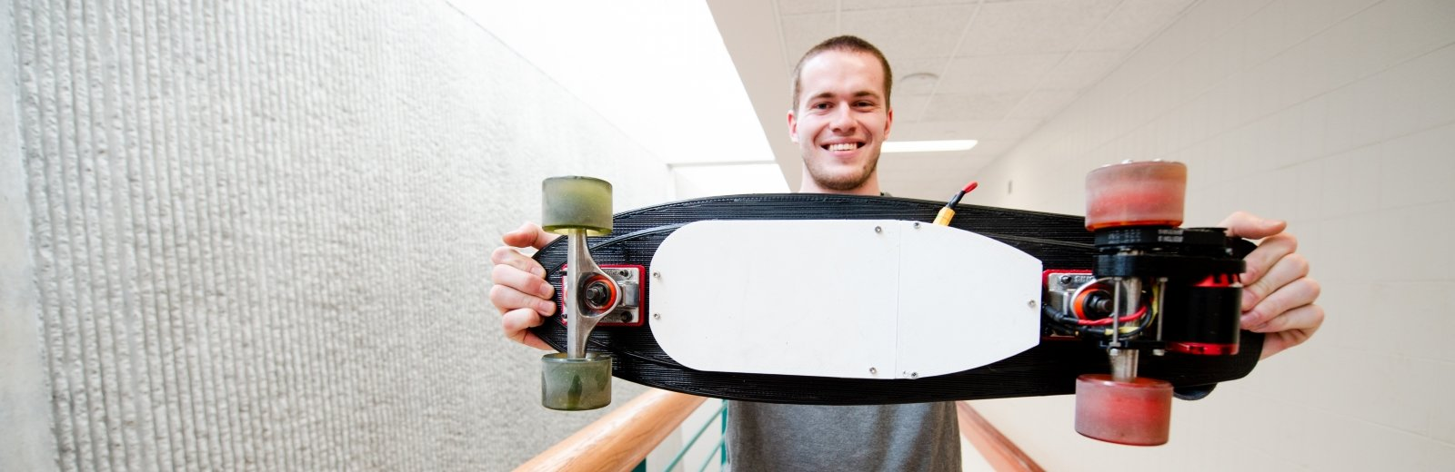 man holding a skateboard, wheels toward the camera