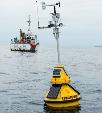 A Michigan Tech buoy floats in the waters of the Straits of Mackinac, with the research vessel Osprey in the background.