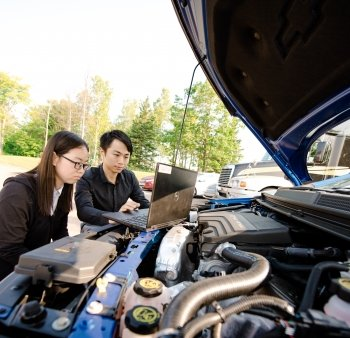 two people working on a laptop under the hood of a car