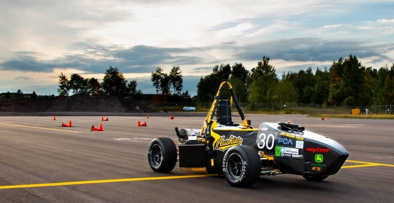 A formula collegiate design car with a Huskies sticker on it in September at a test track with a yellow line and blue sky in the background
