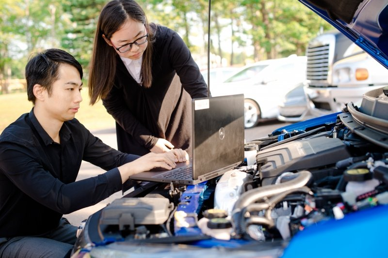 two people in front of a computer balanced on the hood of a car