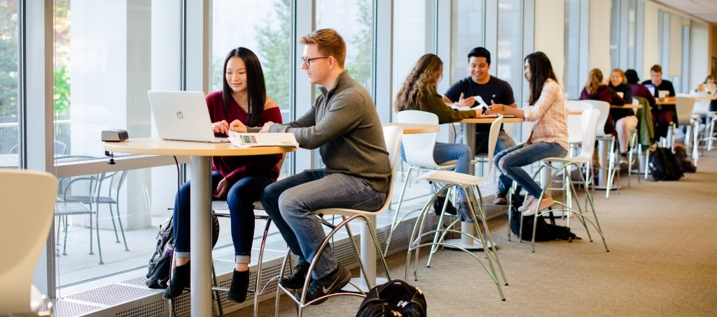 Michigan Tech students study at high tables at the Van Pelt and Opie Library
