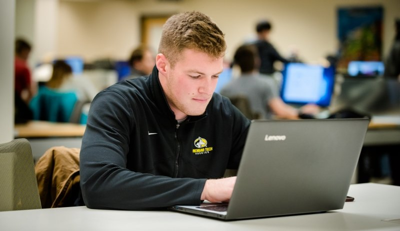 Michigan Tech student working at a computer and wearing clothing with the University's spirit mark.