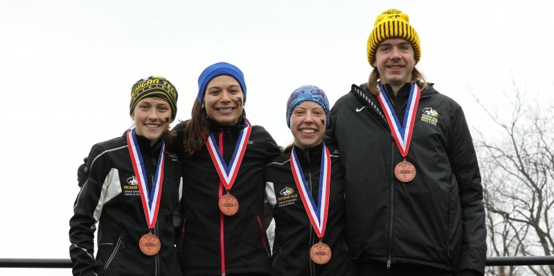 Four members of Michigan Tech's cross country running team wearing medals.