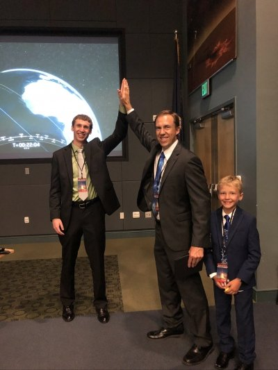 two men is suits and ties do a high five with a planetary screen and an exit sign behind them while a young boy in a suit and tie smiles in front of them