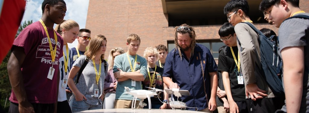A group of students gathers around James Bialas, who has an aerial drone and drone controller in front of him.