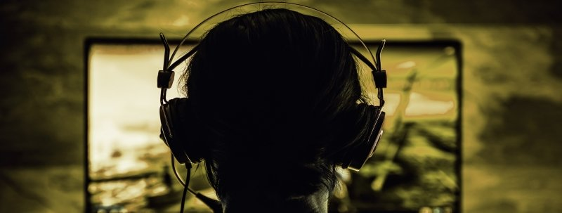 A woman wearing a headset plays a computer-based video game