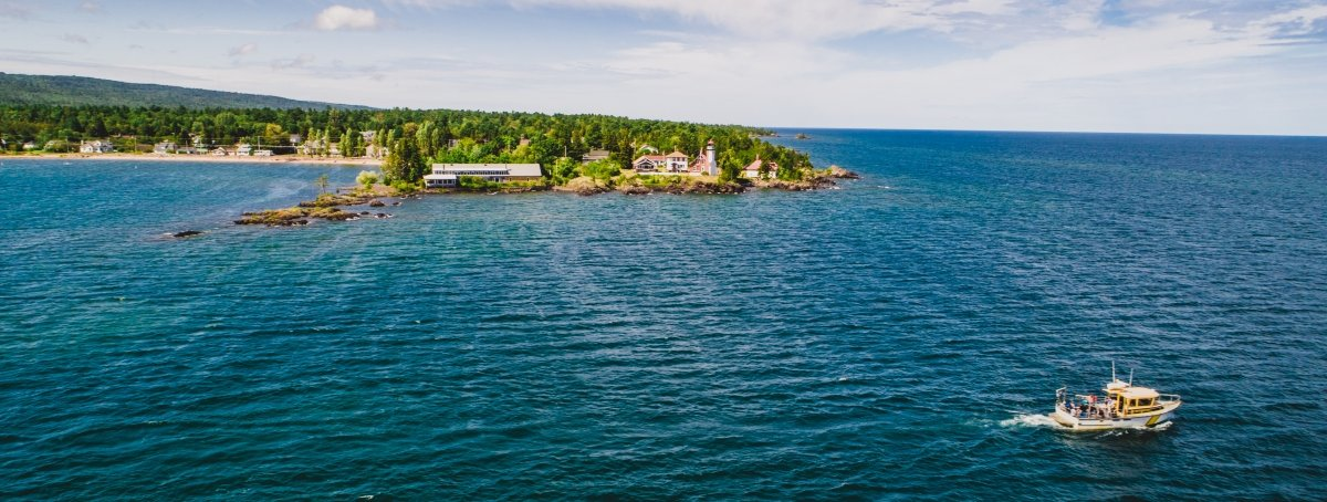 A yellow steel-hulled vessel travels the blue waters of Lake Superior in front of the Eagle Harbor Lighthouse off the Keweenaw Peninsula, a drone shot showing students aboard doing research.