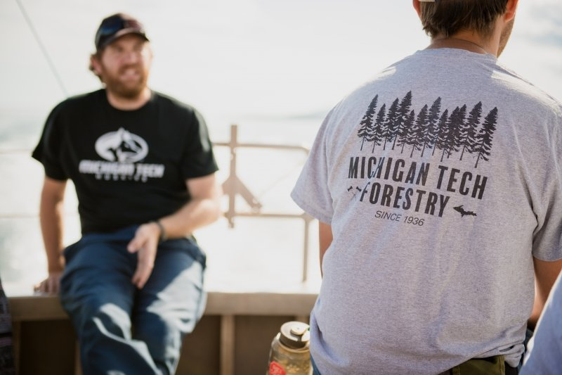 A man with a beard and cap and a Michigan Tech t-shirt faces the camera and a man with a Michigan Tech School of Forestry shirt shows the back of his shirt to the camera with water spray on a boat in the background.