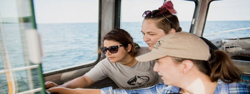 three students look at a laptop screen in the pilothouse of a boat with blue water in the background
