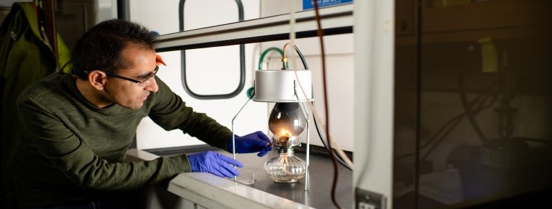 A man looks at a kerosene lamp hooked up to a vacuum under a laboratory vent hood.