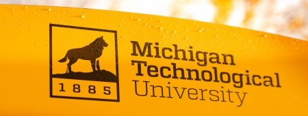 Michigan Technological University sign with 1885, dog on rock, and melty snowflakes
