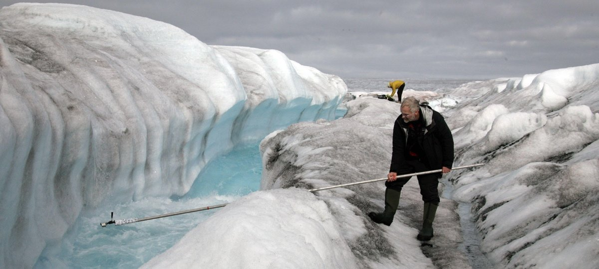 A man in the foreground of a melting glacier with blue water holds a long camera boom into the ice melt as another man stands in the background on an ice sheet.