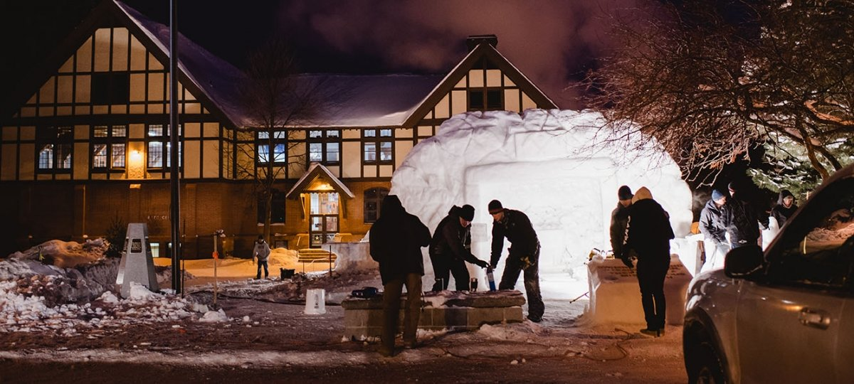 Students working on snow statue at night