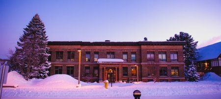 Exterior of Michigan Tech's College of Business in winter at dusk