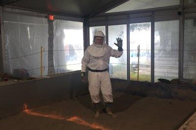 man in haz mat suit standing on gray dust