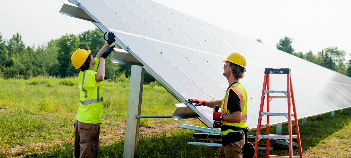 Two men wearing construction vests and hard hats attach a solar panel to its footing.