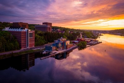 The buildings of Michigan Tech along the Keweenaw Waterway at sunset.