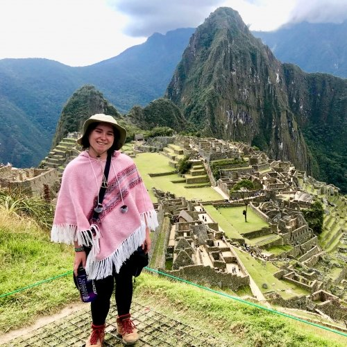 A young woman in a pink poncho, hat, and hiking boots smiles above Machu Picchu in Peru with the Andes Mountains in the background.