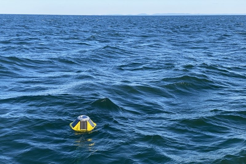 A Spotter buoy in the water with the Huron Mountains on the horizon.