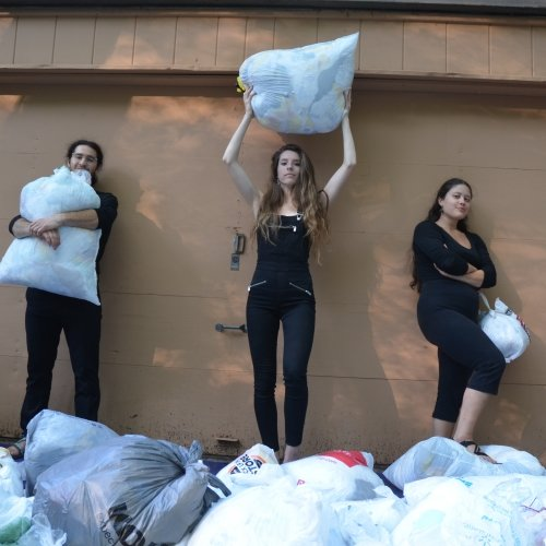 A young man in center and two young women stand holding a plethora of plastic bags in front of a wooden garage wall