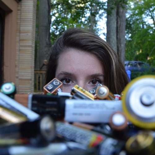 a woman's face behind a pile of collected batteries with a brick building and woods in the background