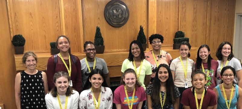 A woman in a polka dot dress with 13 students in summer clothes in front of a fireplace and wood paneling with the Michigan Technological University seal above at a summer STEM workshop