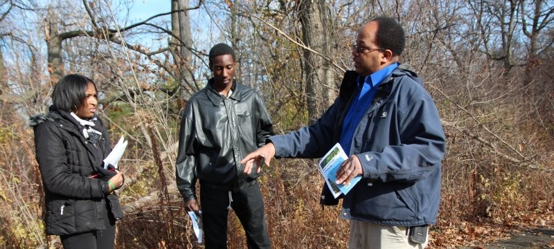 A Black educator talks with two Black High School students about natural resources careers on the sidewalk next to a late-fall forest in a STEM outreach program focused on the environment