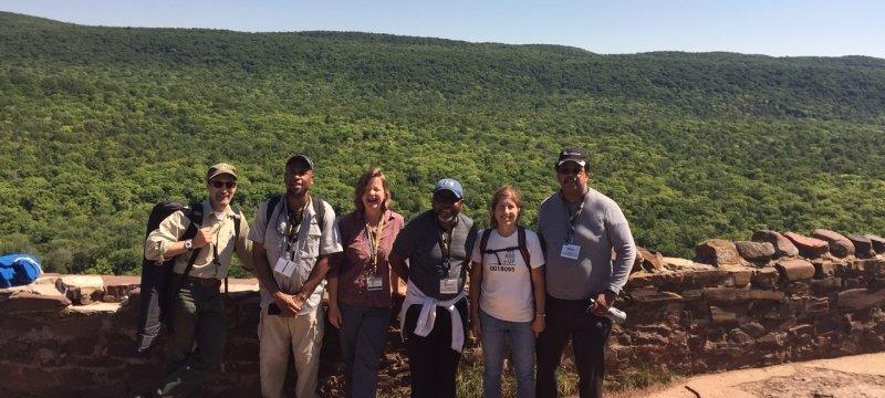 Six teachers in hiking gear on Keweenaw Peninsula's Brockway Mountain with a Rock wall behind them.