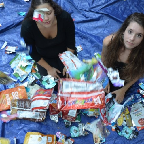 foil wrappers float around two young women on a blue tarp outside