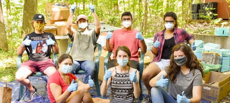 A group of eight students with COVID-19 masks on sitting outside in the woods on a tarp with a brick house behind them and egg cartons and boxes around them. (Photo by Ranit Karmakar)