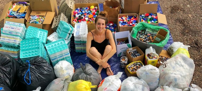 A young woman sitting in the center of recycled egg cartons, foil-lined wrappers, bottle caps, plastic bags and batteries.