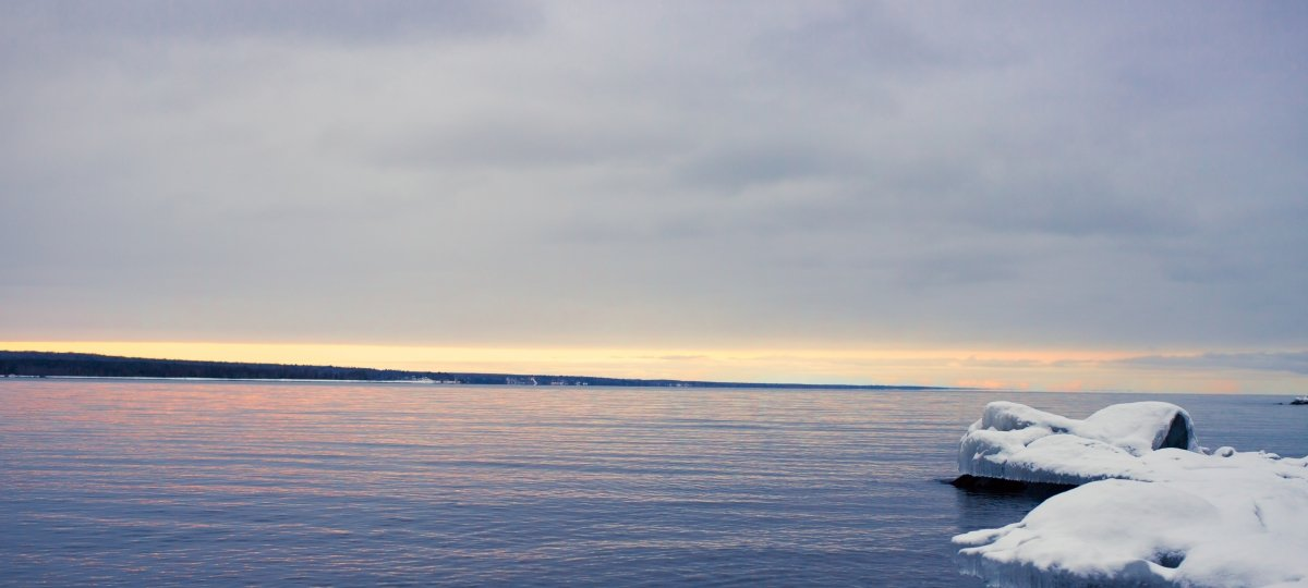 Keweenaw Bay with ice-covered rocks in the foreground of the image and a sunrise just beginning to peak through the clouds.